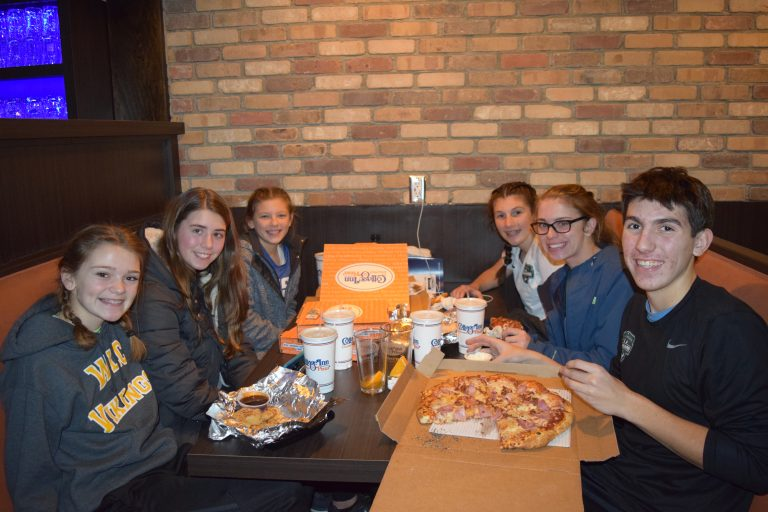Six people enjoying some pizza at a Cottage Inn restaurant.